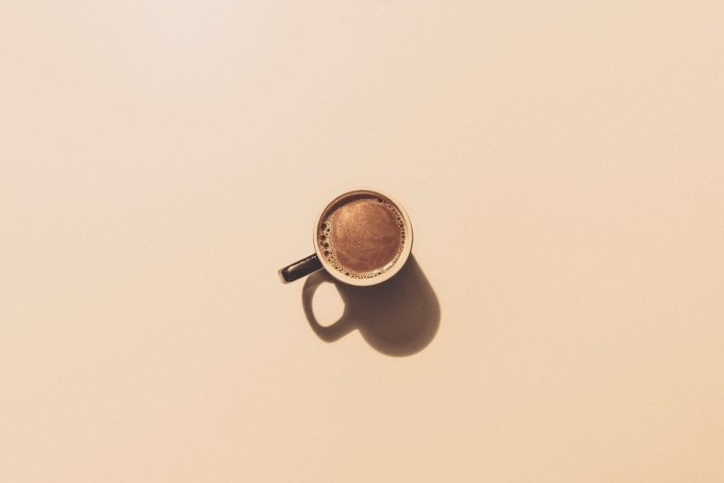 Flat-lay shot of coffee in ceramic cup on brown backdrop