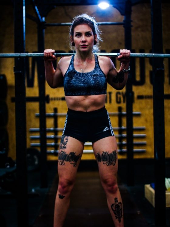 A woman with a barbell across her shoulders.