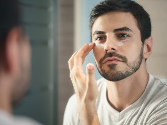 Hispanic male applies anti-aging cream to his face