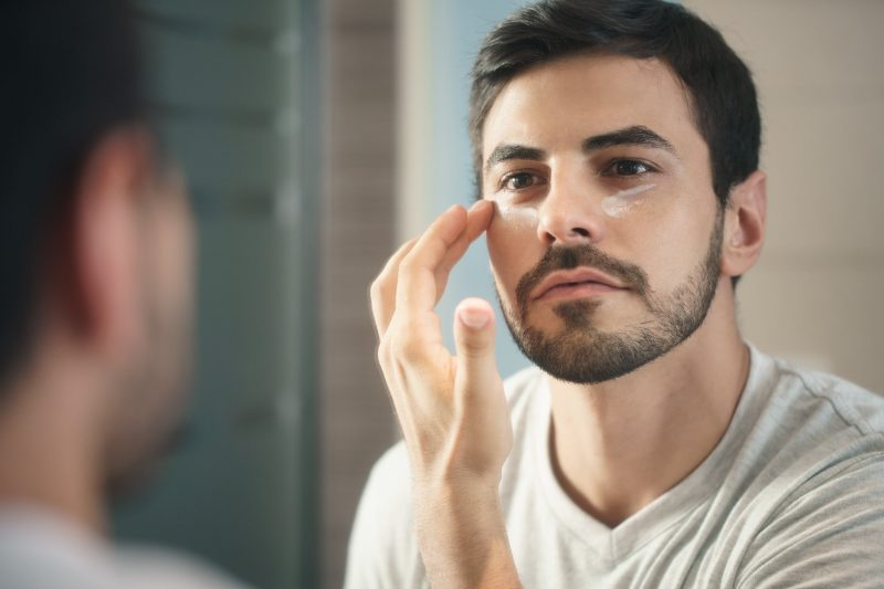 Hispanic male applies anti-aging cream to his face