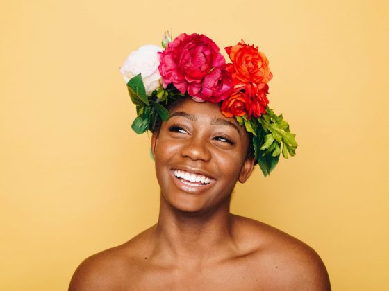 A woman wearing a flower crown in front of a yellow background, smiling.