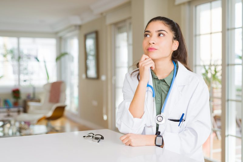 Young doctor woman wearing medical coat at the clinic with hand on chin thinking about question, pensive expression. Smiling with thoughtful face. Doubt concept.