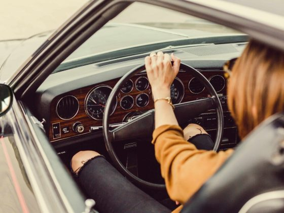 Woman at the wheel of a classic Ford Mustang.