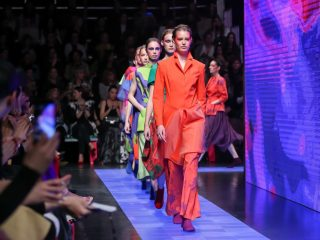 A line of models walk the runway at a fashion show