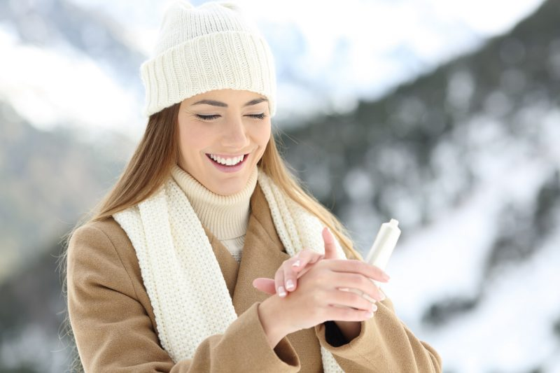 Happy woman hydrating hands skin with moisturizer cream in a snowy mountain in winter