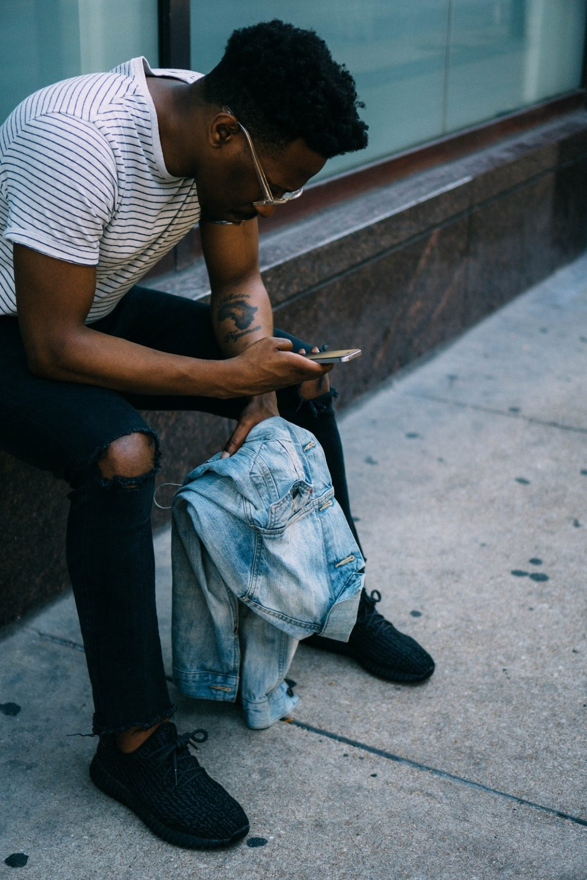man sitting on the side of a building looking at his phone