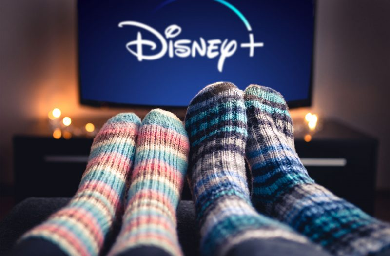 two pairs of feet up with a tv showing disney plus in the background