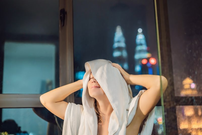 Beautiful woman wipes her hair after a shower on the background of a window with a panoramic view of the night city.