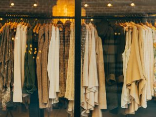 A rack of beige clothing in a vintage store through a window