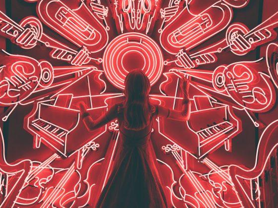 lsdy standing infont ofv red neon lights