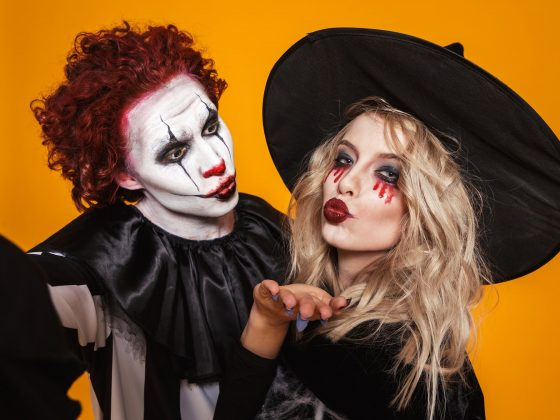 scary clown and wizard in halloween costumes making selfie to camera isolated over orange