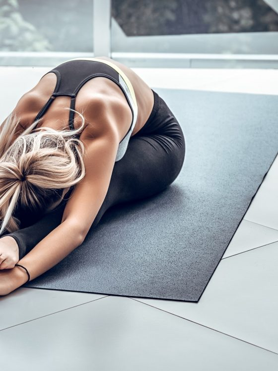 blonde woman stretching on a yoga mat reaching her toes