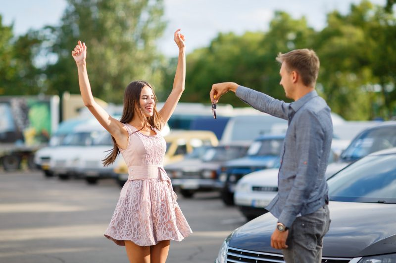 girl in pink dress exclaiming in happiness after buying a car with car finance