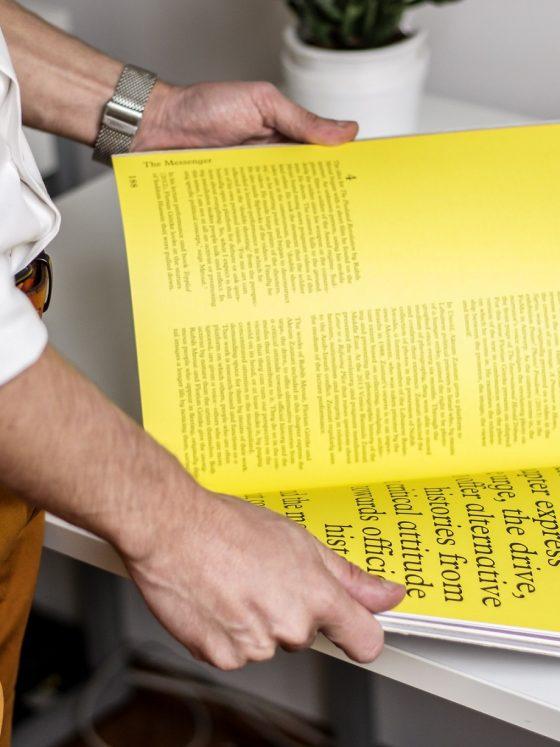 man holding a yellow print zine