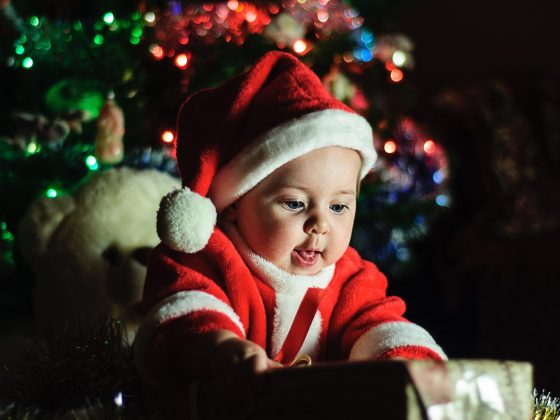 baby dressed in santa outfit opening a gift, with christmas tree in the background