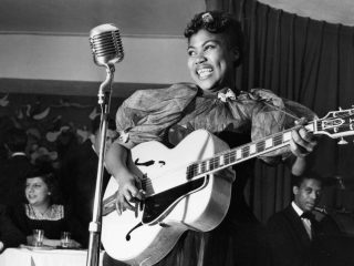 Sister Rosetta Tharpe performing in front of a crowded bar.