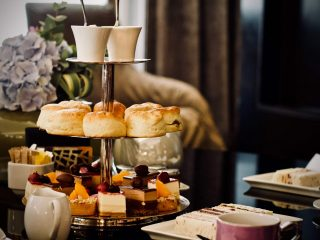 scones on tall tray next to tea set on fine hotel table