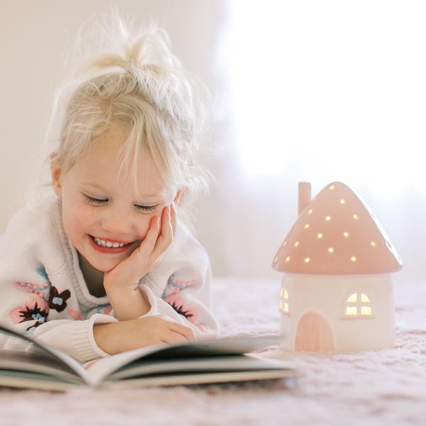 happy little girl lying down on her bed next to a night light, reading a book in her room