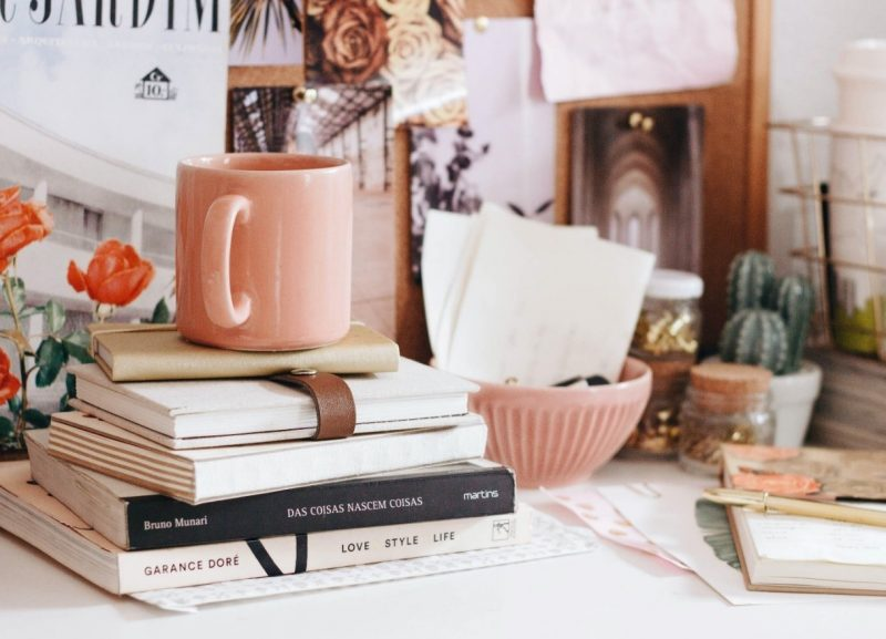 A desk with many pink items on it, including a pink mug, pink bowl, and some pink books.