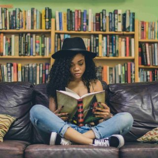 A woman sitting on a couch reading a book with bookshelves behind her.