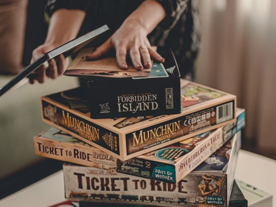 man choosing from collection of board games on top of a table stacked on top of each other