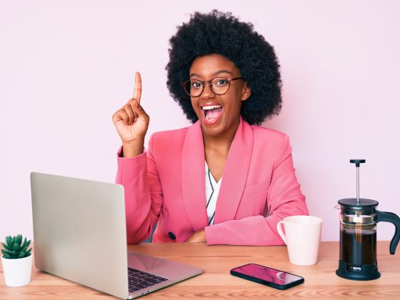 Young african american woman working at desk using computer laptop smiling with an idea or question pointing finger up with happy face,