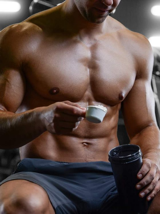 Man in gym mixing supplement drink