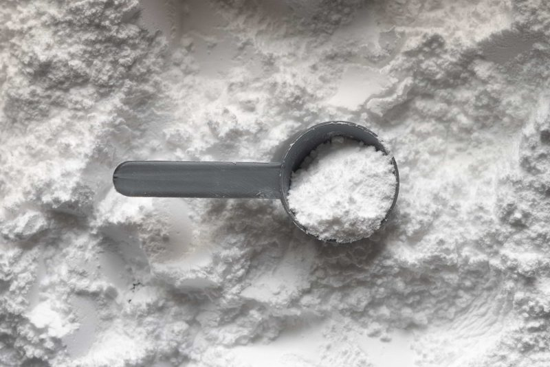 A scoop of creatine powder sitting on top of more creatine powder