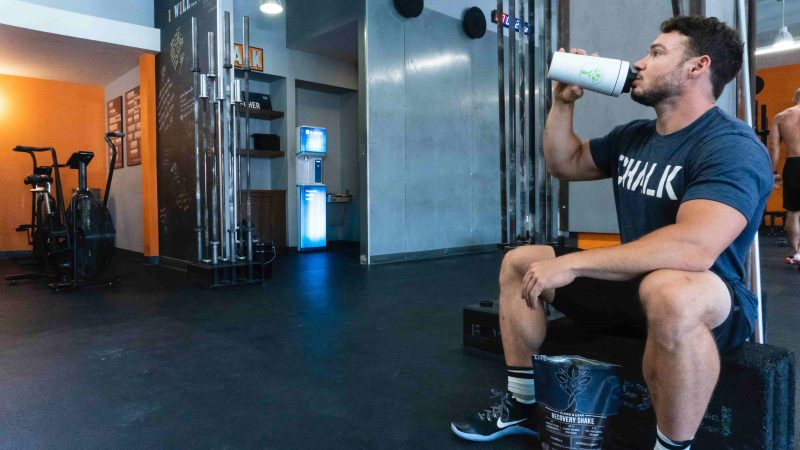 A man sitting in the gym while drinking protein powder